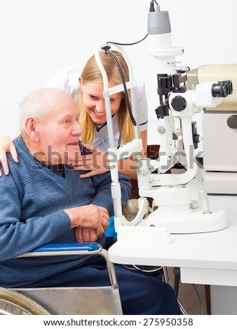 Young helpful doctor with senile elderly patient at an optical exam. - stock photo