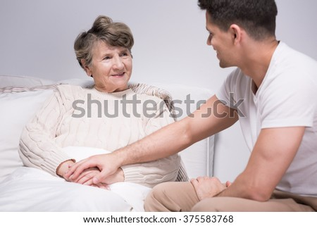 Young helpful grandson spending time with grandmother - stock photo