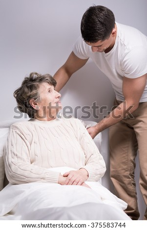 Young helpful man straightening older woman's pillow