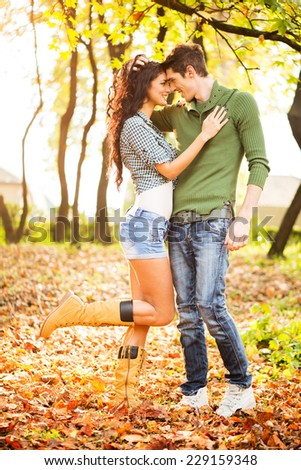 Young heterosexual couple in love in park, standing on fallen leaves, leaning their heads at each other, looking at each other and smiling. - stock photo