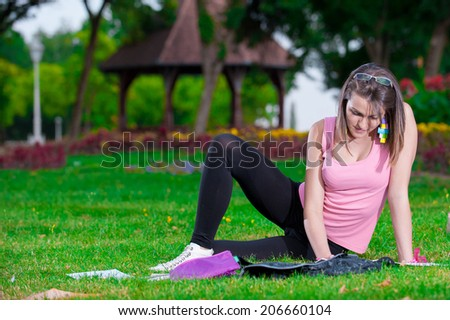 young high school student or college girl lying on the grass in the park and learn/happy young high school student - stock photo