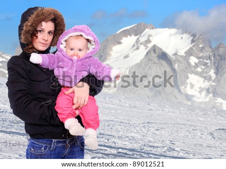 Young highlander with her baby dressed in a fur in snowy mountains. Seasonal fashion shot.