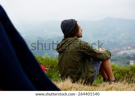 Young hike hipster man sitting at his campsite on the top of hill while enjoying the nature in rainy weather, young man relaxing on the grass enjoying outdoors view and relaxing after hike way - stock photo