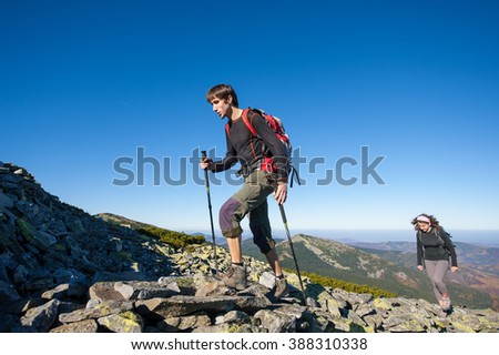 Young hiker couple climbing up rocky the mountain top, high altitude. Beautiful autumn mountain landscape on the background. Fall. - stock photo
