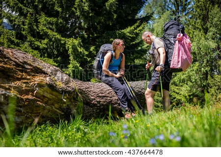 Young hiker couple sitting and resting in the forest after a long hike in the mountains in a sunny vacation. - stock photo