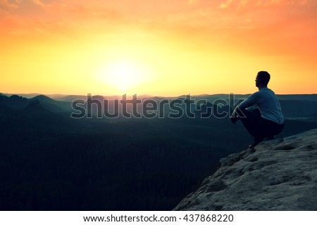Young hiker in black and shirt is sitting on cliff's edge and enjoyingspring morning in nature. View into misty hilly valley bellow