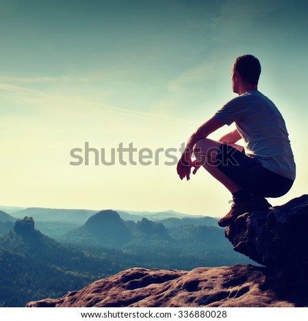 Young hiker in black pants and shirt  is sitting on cliff's edge and looking to misty hilly valley bellow - stock photo