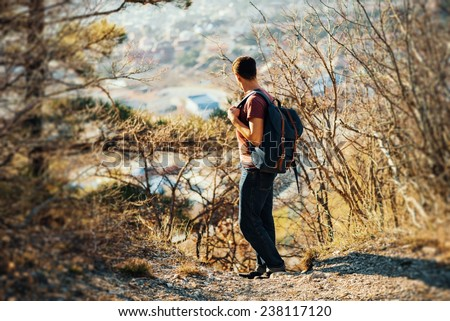 Young hiker man with backpack looking back in autumn outdoor in highlands. Hiking and recreation theme - stock photo