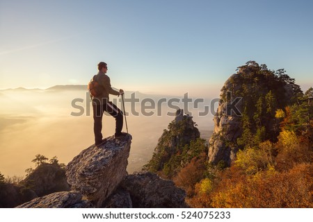 Young hiker man with backpack standing on top of the mountain.