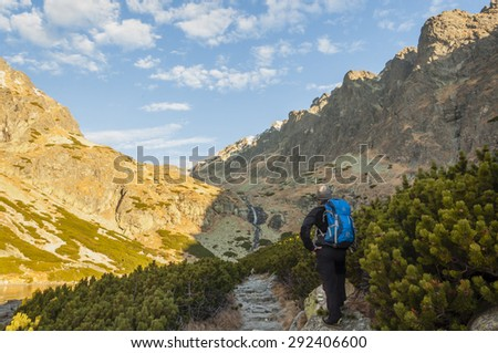 Young hiker on the trail we look at the peaks and waterfall  - stock photo