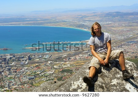 Young hiker sits on rock - bird-view background. Shot in Table Mountain (cable car area), Cape Town, South Africa.