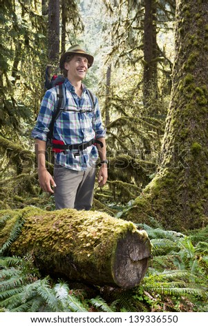 Young Hiker, standing in a temperate rain forest, wearing a hat and a backpack, surrounded by moss covered tree trunks, ferns and spruce trees - stock photo