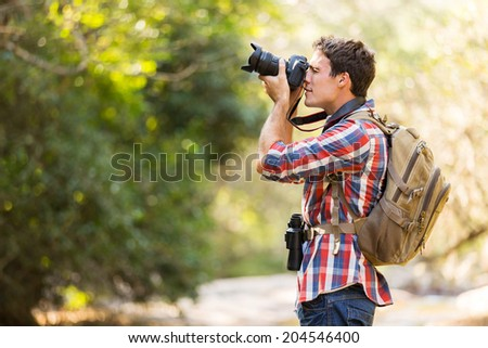 young hiker taking photos in mountain valley - stock photo