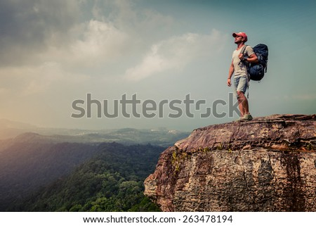 Young hiker with backpack standing on top of the mountain - stock photo