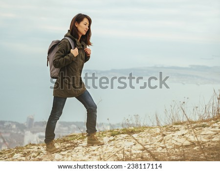 Young hiker woman with backpack walking in highlands on background of sea. Hiking and recreation theme - stock photo