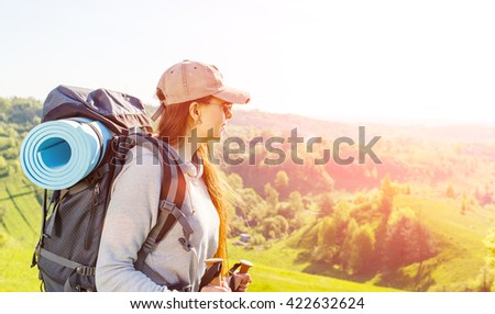 Young hiker woman with backpack walking in the mountains. Traveling vacation background with copy space - stock photo