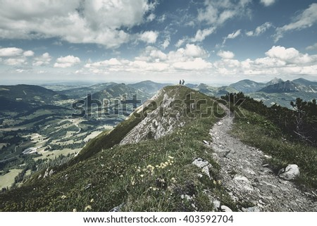 Young hikers holding hands and enjoying beautiful alpine valley standing on top of mountain - adventure concept - stock photo