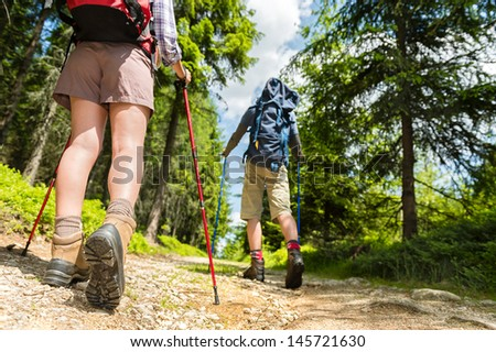 Young hikers walking with trekking poles - stock photo