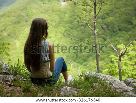 Young hiking brunette beauty relaxing at rocky vista point. - stock photo