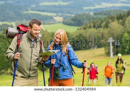 Young hiking couple with friends looking map to find track - stock photo