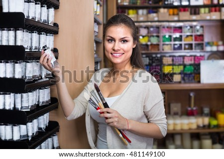 Young hilarious woman choosing various color in tube in art store