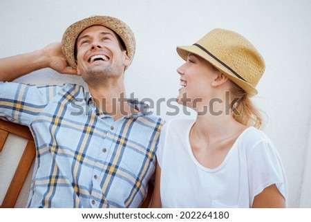 Young hip couple laughing on bench on a sunny day in the city - stock photo