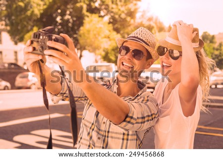 Young hip couple taking a selfie on a sunny day in the city - stock photo