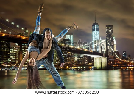 Young hip hop couple dancing, over urban background - stock photo
