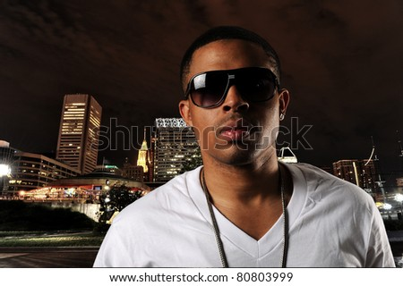 Young Hip Hop Dancer portrait with city skyline on the background at night - stock photo