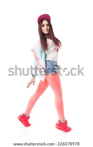 Young hip-hop swag girl in pink tight leggings, crop top and in denim shorts with red hair. Female dance girl in a pink cap and sneakers with tattoo isolated on white background. - stock photo