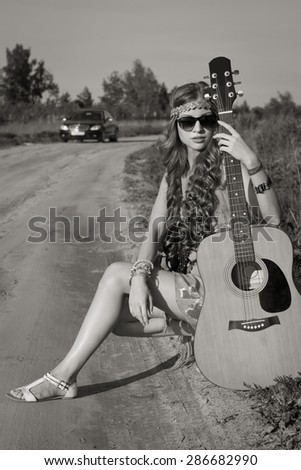 Young hippie girl sitting on a summer field with her guitar - stock photo