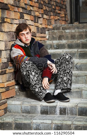Young hippie man sitting on the steps - stock photo