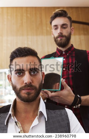 young hipster barber shows haircut to a customer - stock photo