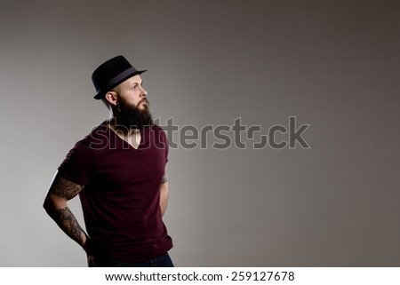 young hipster bearded man wearing hat - gray background - stock photo