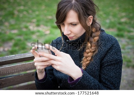 young hipster beautiful woman using device tablet at the park