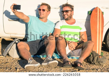 Young hipster best friends taking a selfie sitting next to the car - Concept of modern technologies mixed with vintage lifestyle - Adventurous friendship during travel and vacation - stock photo