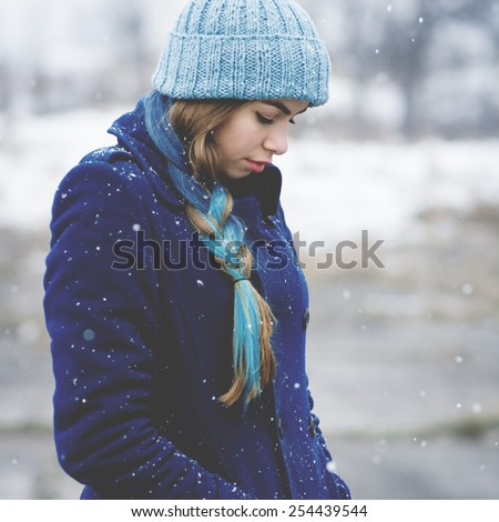 Young hipster Caucasian teenage woman with long partly dyed blue braid. Adolescent girl in blue coat and knit beanie hat outdoor in winter. Mild retouch, matte blue toned filter applied, square format - stock photo