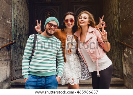 young hipster company of friends traveling, vintage style, europe vacation, sunglasses, old city center, happy positive mood, smiling, embracing, showing peace sign