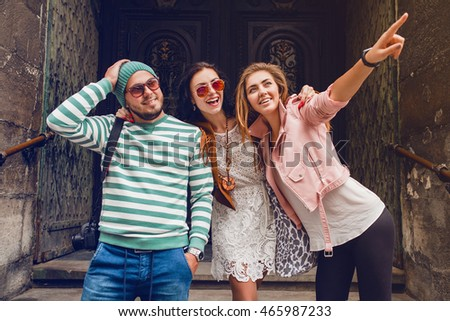 young hipster company of friends traveling, vintage style, europe vacation, sunglasses, old city center, happy positive mood, smiling, embracing, pointing finger, looking forward