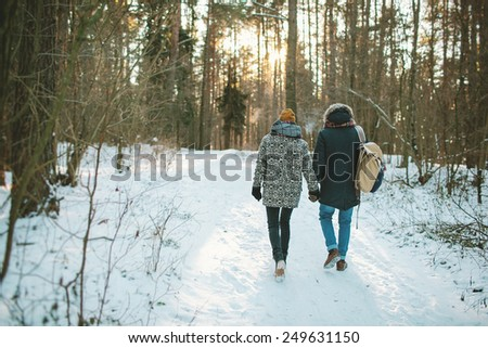 Young hipster couple having a walk in winter forest with bag alone - stock photo