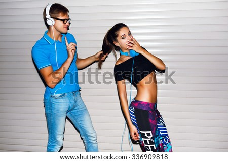 Young hipster couple having fun going crazy at romantic date,  listening music at big headphones, party time, bright sportive clothes, urban wall background, joy, emotions, surprised , fit couple. - stock photo