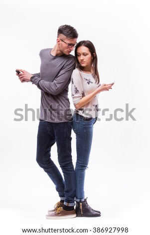 Young hipster couple ignoring each other using their smart-phones. He look at her phone, she looks at his. Caucasian couple against white background. - stock photo
