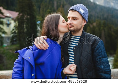 young hipster couple in love on winter vacation in mountains, embracing, kissing, warm outfit, knitted cap, blue jacket, forest, jeans, coat, smiling, having fun, traveling, hiking