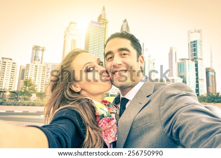 Young hipster couple in love taking a selfie at Dubai city skyline - Concept of fun and interaction with new trends and technology - Vintage filtered look with sun flare and soft focus on the faces - stock photo