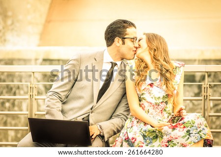 Young hipster couple kissing while sitting with laptop and smartphone - Modern concept of love with businessman and beautiful woman in urban business area outdoors - Warm saturated filtered look - stock photo