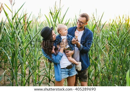 Young hipster family with cute baby in hands in the cornfield smiling and playing - stock photo