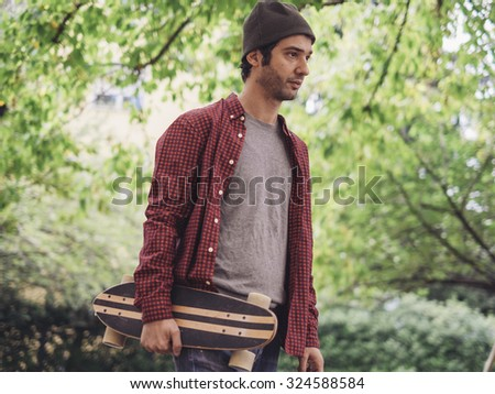 Young hipster fashion guy and his skateboard  - Traveler man and retro nostalgic filtered look - stock photo