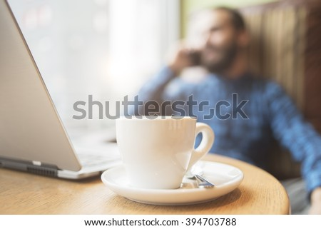Young hipster fashion man working on laptop in coffee shop - stock photo