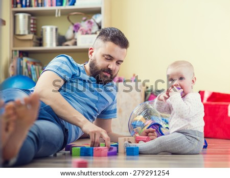 Young hipster father playing with his daughter on a floor - stock photo