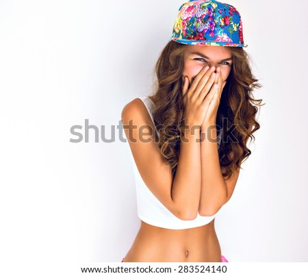 Young hipster girl going crazy, have positive surprised emotions, screaming and laughing, bright summer outfit. close her face by her hands. - stock photo